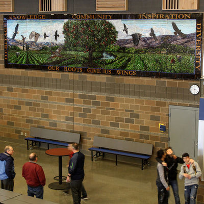 "This project was done in cooperation with the Washington State Arts Commission for the new high school in Wapato, WA. These are 2 glass mosaic murals created for Wapato High School. The first mural consists of 7 panels, the total dimensions are 7ft x 28ft wide and is located in the commons area.  The image symbolizes how the roots of heritage, community & family give wings to the individual, helping them to learn, grow and fly out into the world and plant their own roots.  The variety of bird species that flow out from the central tree represent the diversity of the community and the individuals nurtured by the community going forth into the world.  The areas roots in agriculture are represented in the central apple tree, which also a represents the community as a whole and the concepts of growth, learning, family and inspiration. The hills in the background and the cultivated fields further celebrate the rich heritage of the area.  <br><br> The second mural is 4 panels installed to create one mural measuring 67"" tall by 14' wide.  The image is of a pack of wolves running through the hills, with the word ""community"" underneath. This represents the concept of strength and growth through working together, playing to each individual's strengths and abilities to create something better for all. <br><br> ​Wapato High School Public Art Project, 2016 Glass Mosaic in two murals, Our Roots Give Us Wings 7ft x 28ft and Community 6ft x 14ft.  Two murals created in collaboration with the Washington State Arts Commission and the art committee of the new Wapato High School in Wapato, WA.  The Roots and Wings mural carries the theme of the students honoring their roots in this diverse community and using those roots as a springboard to carry them into their individual futures.  The Community mural honors the cohesiveness of the tight knit community and the support the members give to one another."